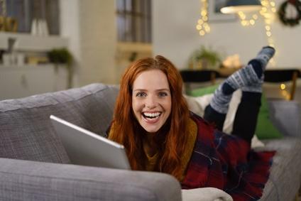 glückliche frau liegt abends auf dem sofa und liest am tablet
