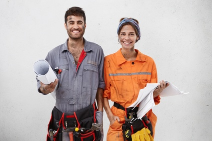 Joyful handyman and female architect collaborate together, wear working clothes, hold sketches with new construction plan, smile broadly, stand next to each other over white blank studio wall